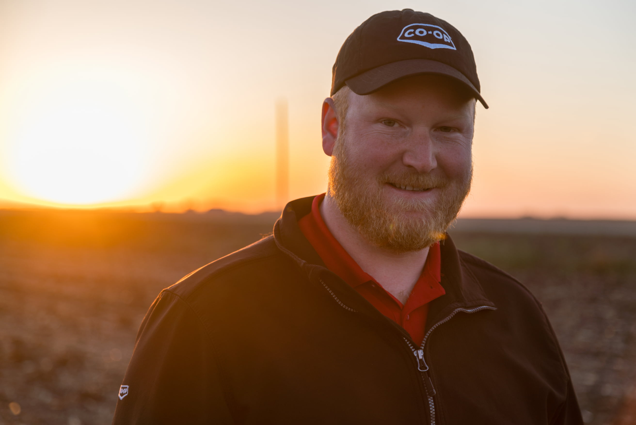 Man with a Co-op ball cap in a field, smiling at the camera with a sunset in the background.